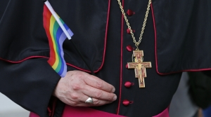 Faith leader holds a rainbow flag next to a crucifix