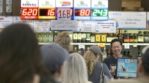 People wait in line to purchase lottery tickets for the Mega Millions lottery
