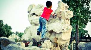 Child climbing rock formation