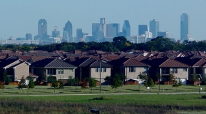 row of similar suburban houses, city skyline in background