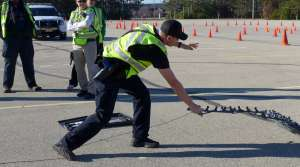 Recruit Nick Pine practices deploying stop strips, which can damage a fleeing vehicle's tires during a high-speed pursuit.