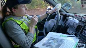 Recruit Stephanie Nelson uses her squad car's radio during a training exercise.