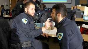 Recruits Ruben Gonzalez and Ercan Dzelil practice using a breathalyzer.