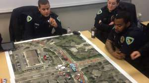 Madison Police recruits learn to stage emergency vehicles at the site of a traffic crash using a map of Madison and matchbox cars.