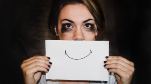 A woman holding a smile on a piece of paper in front of her mouth