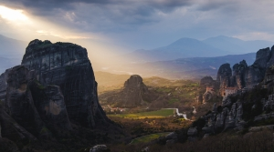image that is a view from a Greek mountain top through a valley to the ocean