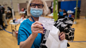 A person holds up their Covid-19 vaccine card