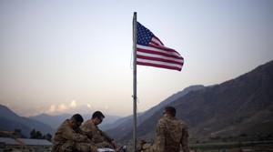 American soldier sit beneath an American flag in Kunar province, Afghanistan