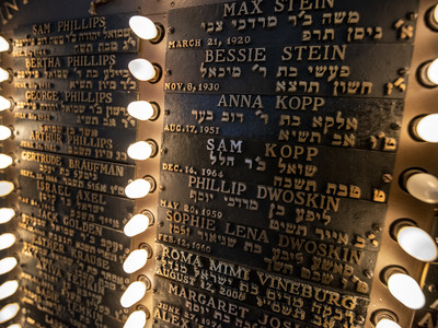 small lights illuminate names written in gold text on a plaque.