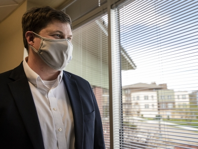 A man in a face mask stands near a window.