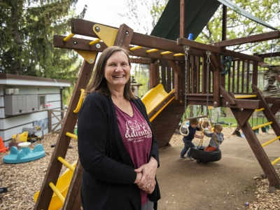 Sike O'Donnell stands in front of the playground as two children swing on a tire swing behind her.