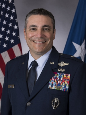 Brigadier General Paul Knapp sits for a portrait in his blue Air Force uniform. His jacket is covered in awards. He smiles in front of an American flag.