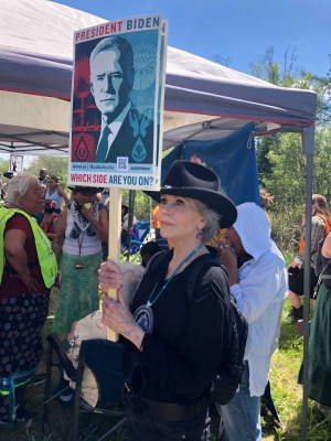 Jane Fonda holds a sign with a picture of Joe Biden