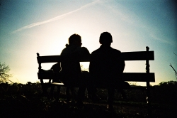 Two people siting on a bench.