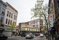 Cars drive by businesses in downtown La Crosse.