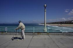 An elderly man walks on a pier
