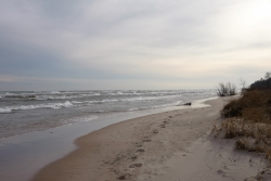 A picture of the sandy beach along the shore of Lake Michigan with foot prints in the sand.