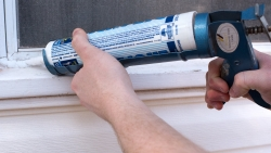 Using caulk to seal window on the outside.