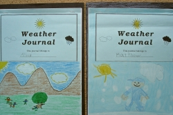 Two weather journals with illustrations on the cover created by students.