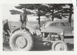 Gary Jones as a child standing on the wheel of a tractor on his family farm.