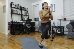 A woman does a lunging pose on her yoga mat in her home with a computer desk setup in background.