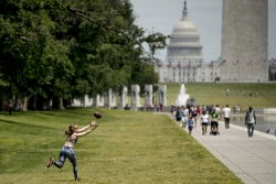A woman catching a football in front of U.S. Capitol