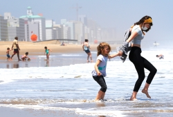 A woman and child play in the surf in Virginia Beach