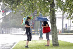 A mom and son stand under their umbrellas in a grassy area near the bus stop.