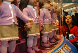 Girl looking at American Girl dolls