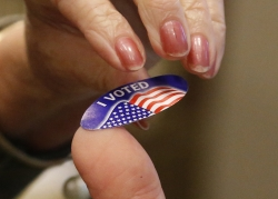 """woman takes an """"I Voted"""" sticker"""