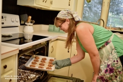 A woman adjusts a baking sheet of cookies in the oven with a mitt.