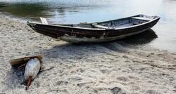 Old rowboat on sandy beach.
