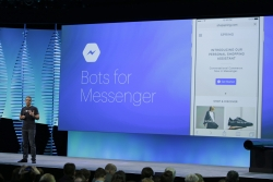 A conference speaker stands in front of a presentation screen talking about the plan for bots on Facebook's messenger app.