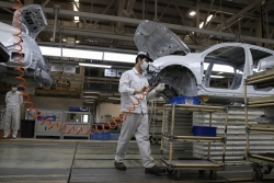 Auto worker assembles car in a manufacturing facility in China
