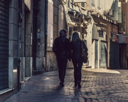 Two people walk down a cobble-stoned alleyway holding hands.