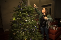 A women wearing a face mask strings a Christmas tree