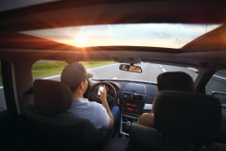 Two people driving into the sun