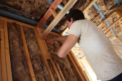 Man insulating walls of house.