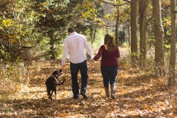 Couple walking dog on trail in fall.