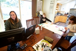 In this Tuesday, March 17, 2020 photo Kim Borton, left, works from home with her children