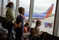 A family wearing masks waits to board a Southwest Airlines flight