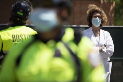 A doctor from Massachusetts General Hospital stands in counter-protest across the street from a demonstration calling for the lifting of all government restrictions related to concern about the spread of COVID-19.