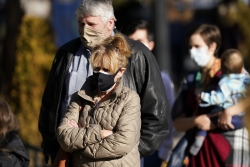 People wearing masks line up outdoors
