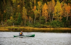 Fishing in a canoe on a fall day.