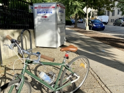 A bicycle in front of a secure voting box.