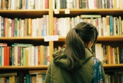 We see the back of a girl with a long, dark hair in a ponytail as she faces a large bookshelf, broswing.