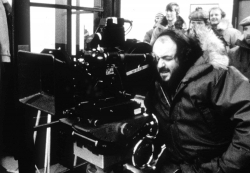 Filmmaker Stanley Kubrick looks through the viewfinder of a camera on set