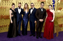 The cast of Schitt's Creek stand for a photo in formal wear.