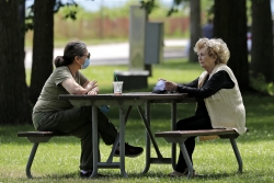 Two people sit apart at a picnic table