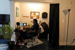 A teacher sits at her desk with a mic, laptop and several screens in her own home.